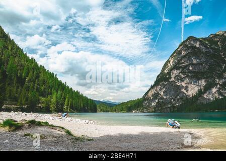 Kleine Mädchen, die am Strand des Sees in den Bergen spazieren gehen - Stockfoto