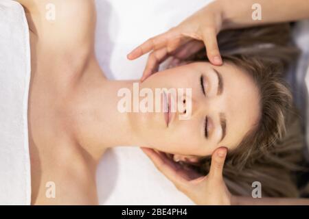 Junge blonde Frau, die in einem Spa-Center eine Kopfmassage erhält. - Stockfoto