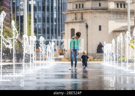 Birmingham, Großbritannien. April 2020. Die 12-jährige Mia nimmt ihren 18 Monate alten Bruder Jasper mit auf ihren täglichen Übungsgang durch die Brunnen am Centenary Square im Stadtzentrum von Birmingham. Ihre Familie lebt in der Nähe. Der Ostersonntag hat als warmer und sonniger Tag begonnen. [Elterliche Erlaubnis erteilt] Credit: Peter Lopeman/Alamy Live News - Stockfoto