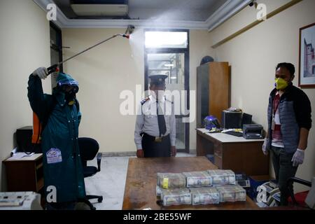 Kathmandu, Nepal. April 2020. Ein Mann, der einen Schutzanzug trägt, desinfiziert Banknoten, da er Bedenken wegen der Ansteckung des Coronavirus hatte, am 20. Tag der Regierung, die am Sonntag, dem 12. April 2020, die Himalayan Bank in Kathmandu, Nepal, gesperrt wurde. Kredit: Skanda Gautam/ZUMA Wire/Alamy Live News - Stockfoto