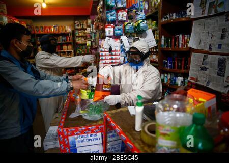 Kathmandu, Nepal. April 2020. Ein Verkäufer, der einen Schutzanzug trägt, bedient einen Kunden angesichts der Bedenken wegen der Ansteckung des Coronavirus am 20. Tag der vom Staat auferlegten Lockdown bei der Himalayan Bank in Kathmandu, Nepal, am Sonntag, den 12. April 2020. Kredit: Skanda Gautam/ZUMA Wire/Alamy Live News - Stockfoto