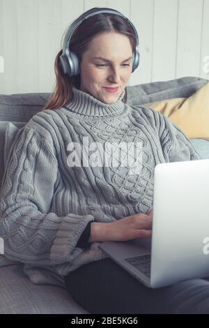 Junge Sommersprossen Frau sitzt auf dem Sofa in einem modernen skandinavischen Wohnung. Sie erfüllt ihre Freizeit zu Hause mit digitaler Unterhaltung. - Stockfoto