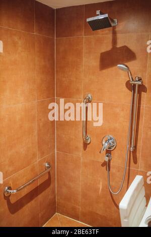 Dusche mit Sitz und Haltegriffen für Behinderte und ältere Menschen im Badezimmer - Stockfoto