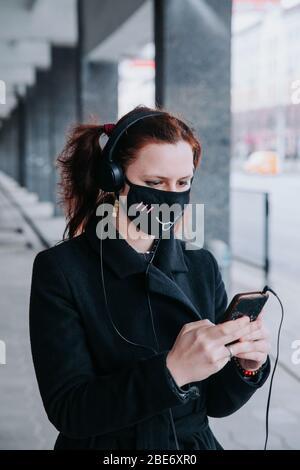 Junge kaukasische Frau trägt lustige Gesicht Schutzmaske Lesen Nachrichten auf ihrem Handy im Freien. - Stockfoto