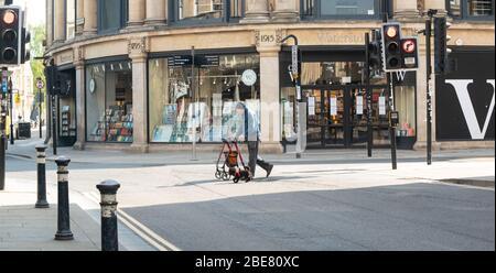Ein behinderter Mann, der einen Gehrahmen auf Rädern benutzt, geht am Ostersonntagmorgen in menschenleeren Straßen, Oxford, Oxfordshire, Großbritannien, mit seinen Hunden spazieren Stockfoto