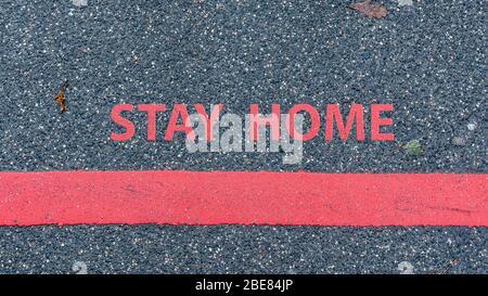 Top Ansicht der Asphaltstraße mit roter Linie und Text ZU HAUSE bleiben, Beschränkung oder Sicherheitswarnung Konzept - Stockfoto