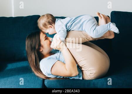 Mutter spielt mit ihrem Sohn. Das Baby lacht. Das Konzept der Kommunikation zwischen Eltern und Kindern, Unterhaltung in Quarantäne, zu Hause bleiben. - Stockfoto