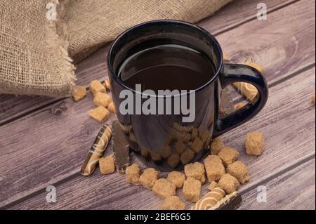 Dunkelblaue Keramik-Tasse mit Tee und Stücken von braunem Rohrzucker auf einem hölzernen Hintergrund. Nahaufnahme - Stockfoto