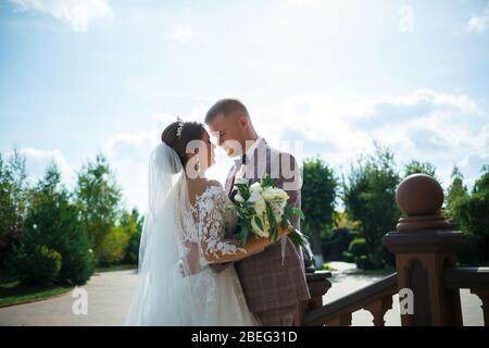 Braut im weißen Kleid und Bräutigam in Kostüm kuscheln und spazieren im Park
