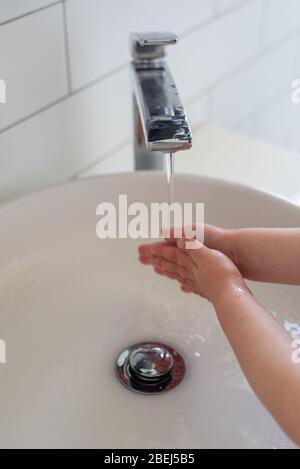 Mädchen waschen Hände unter einem modernen Wasserhahn und sinken während der COVID-19 Pandemie 2020 - Stockfoto