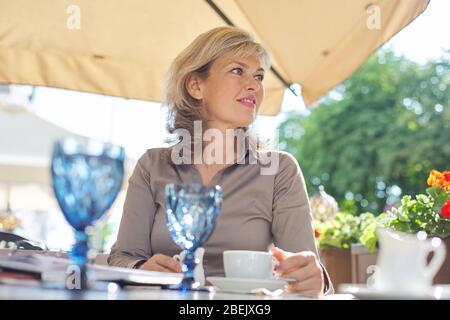 Portait von reifen schöne blonde Frau seitlich schauen, kopieren Raum. Lächelnde Geschäftsfrau mittleren Alters, die Kaffee in einem Café im Freien trinkt - Stockfoto