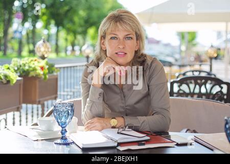 Portait von reifen schöne blonde Frau Blick auf Kamera, lächelnd mittleren Alters Geschäftsfrau trinken Kaffee im Freien Café - Stockfoto