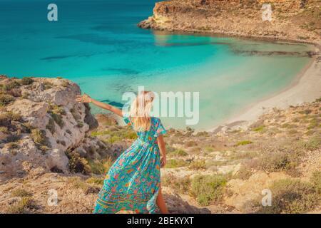 Rückansicht einer jungen blonden Frau, die den fantastischen Blick auf den Kaninchenstrand in Lampedusa genießt, einer paradiesischen Insel, die zu den Pelagie-Inseln südlich von Sizilien gehört - Stockfoto
