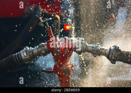 Wasser spritzt von den Löschschläuchen und Hydrantenanschlüssen ab. Feuerwehrgerätehaus. - Stockfoto