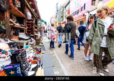 Menschen und Touristen, die vorbeigehen und die Ausstellung von Harajuku Mode-Stil Schuhe zum Verkauf vor einem Geschäft in Takeshita Straße, Harajuku, Japan. - Stockfoto