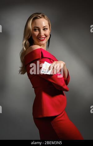Blonde Frau in rotem Kleid und schwarzen Ohrringen. Sie lächelt, zeigt zwei Asse, posiert seitlich auf grauem Studiohintergrund. Poker, Casino. Nahaufnahme - Stockfoto