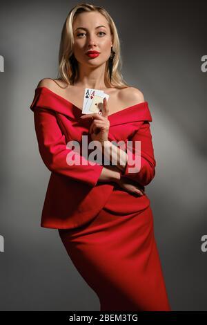 Blonde Dame mit nackten Schultern, in rotem Kleid, schwarze Ohrringe. Zeigt zwei Asse, umarmt sich, posiert auf grauem Hintergrund. Poker, Casino. Nahaufnahme - Stockfoto