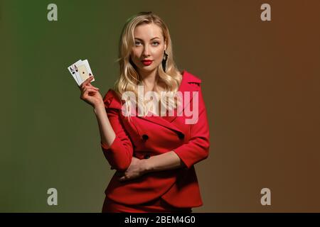 Blonde Frau in rot stilvolles Kleid und schwarze Ohrringe. Sie lächelt, zeigt zwei Asse, posiert auf buntem Hintergrund. Poker, Casino. Nahaufnahme - Stockfoto