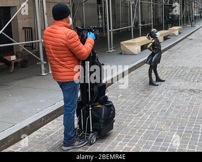 New York, Usa. April 2020. Die Skulptur Fearless Girl von Kristen Visbal ist am 14. April 2020 vor der New Yorker Börse in der Broad Street in New York zu sehen. Es ist nicht bekannt, wer die Maske auf die Skulptur aufsetzt. (Foto: Samuel Rigelhaupt/Sipa USA) Quelle: SIPA USA/Alamy Live News - Stockfoto