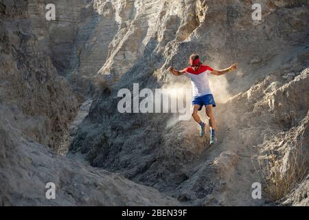 Ein Mann Trail läuft auf technischem Gelände und hinterlässt Staub auf seinem Weg