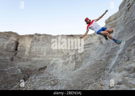 Ein Mann bildet eine 'Wall Ride', während Trail Running auf einem sandigen Gelände