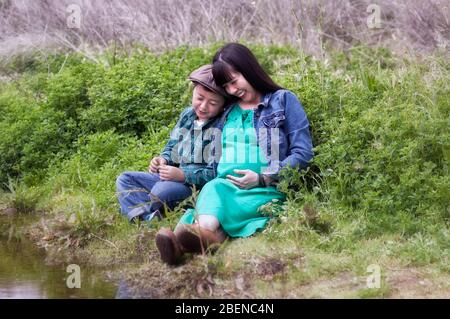 Schwangere asiatische Mutter mit langen schwarzen Haaren in einem grünen Kleid und blauer Denim-Jacke ihr Sohn in einer braunen Newsboy-Mütze lachend zusammen auf einer Wiese - Stockfoto