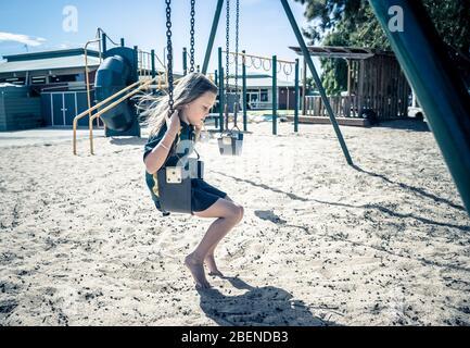 Covid-19 Ausbruchschulen geschlossen. Trauriges und gelangweiltes Schoolgirl fühlt sich depressiv und einsam auf dem leeren Spielplatz, als die Schule geschlossen ist. Einschränkungen und Lo - Stockfoto
