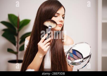 Hübsches Mädchen gilt Make-up auf Gesicht zu Hause in der Nähe Spiegel - Stockfoto