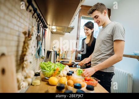 Glückliches Paar genießen Kochzeit zusammen zu Hause Küche.Genießen Sie einfache Momente zu Hause.Herstellung veganer Gerichte.pflanzliche Ernährung.Spaß haben, während Maki - Stockfoto