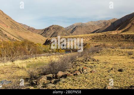 Eine Schlucht in den Bergen mit einem Fluss. Kokemeren Fluss im Jumbal Bezirk der Naryn Provinz Kirgisistan. Steine und Sträucher am Flussufer. - Stockfoto