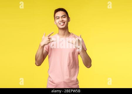 Portrait von cool und stolz gut aussehende Asian Kerl mit großem Ego, zeigen Rock-n-Roll oder Heavy Metal Zeichen und lächelnd, genießen awesome Konzert, Spaß zu haben - Stockfoto