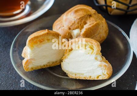 Hausgemachte Profitroles Gebäck mit Pudding mit Tee gefüllt. Eclairs mit Sahne. - Stockfoto