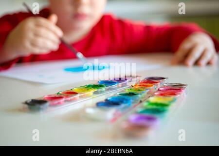Der Junge lernt, mit einem Pinsel auf Papier zu malen, der an einem Tisch sitzt Stockfoto