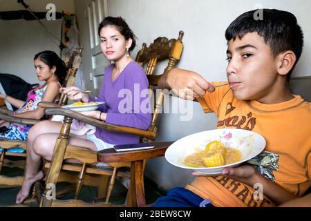 Tatsächliche Szene einer lateinischen Familie, die Mittagessen teilt, haben sie eine traditionelle Mahlzeit aus Mais. Stockfoto