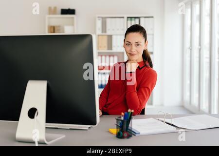 Junge Frau in roter Bluse sitzt am Schreibtisch im Büro und schaut auf die Kamera. Computer- und Büropapier steht im Vordergrund - Stockfoto