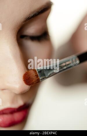Selektiver Fokus der kosmetischen Bürste in der Nähe von Frau mit geschlossenen Augen - Stockfoto