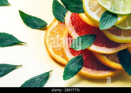 Zitruszitronen-, Limetten-, Orangen- und Grapefruitscheiben und Minzblätter in Flor auf gelbem Hintergrund. Minimaler Designhintergrund. - Stockfoto