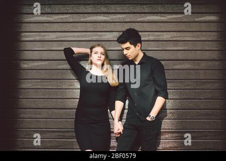 Multirassisches stilvolles Paar in schwarzer Kleidung posiert auf einem Hintergrund einer Holzwand. Türkisch Kerl und kaukasische Frau Datum und Liebe. Lifestyle Elegant Stockfoto
