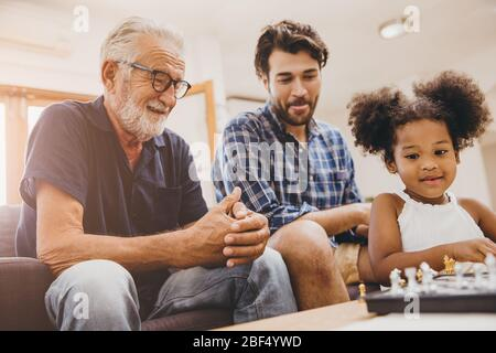 Glückliche Familie Moment Ältester mit Kind kleines Mädchen und Sohn zu Hause Glück Moment spielen Schach.