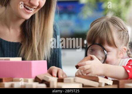 Tochter schaut durch Lupe auf Holzbalken