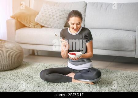 Junge Frau essen lecker Joghurt zu Hause - Stockfoto