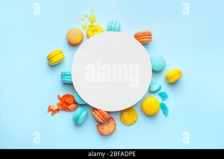 Leckere Macarons mit Papierbogen auf farbigem Hintergrund - Stockfoto