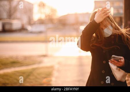 Junge Frau im Schutzgesicht medizinische Maske berühren ihren Kopf, während Sie auf der Straße in der Stadt mit dem Smartphone zu Fuß