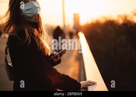 Junge Frau mit Schutzmaske Gesicht medizinische Maske mit Smartphone während das Geländer auf der Brücke in der Stadt bei Sonnenuntergang stehen - Stockfoto