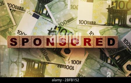GESPONSERTE Wort auf Holzwürfel auf viele 100 Euro Banknoten. Sponsor Finanzierung Finanzierung Finanzierung Business Startup Konzept - Stockfoto