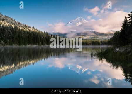 Die Wolken am frühen Morgen lassen den frischen Herbstschnee auf dem höchsten Gipfel von Oregon, dem Mt Hood, erkennen, der sich in Trillium Lake spiegelt. - Stockfoto