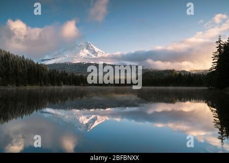 Am frühen Morgen brechen Wolken auf und offenbaren den frischen Herbstschnee auf dem Mt Hood in Oregon, der sich in Trillium Lake spiegelt. - Stockfoto