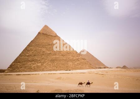 Ein Kamelreiter in der Wüste fährt vor der Pyramide von Khafre am Gizeh Pyramid Komplex in der Nähe von Kairo, Ägypten. - Stockfoto