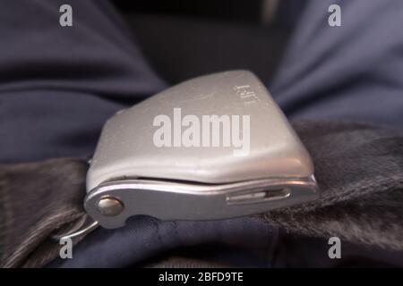 Ein Fluggast mit einem Sicherheitsgurt, der sich verschnallt - Stockfoto