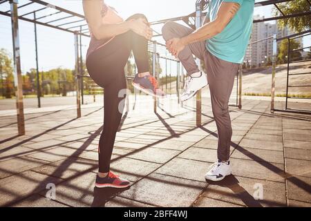 Dehnübungen. Zugeschnittenes Foto von Mann und Frau in Sportbekleidung, die sich beim Stehen im Stadion gemeinsam aufwärmen. Sie sind streckende Beine. Aktiv